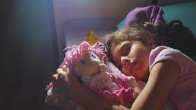 Förtjusande liten flickasömn i soffasängen och att krama henne för att behandla som ett barn - dockan liten brunettflicka som in  stock video