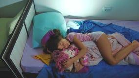 Förtjusande liten flickasömn i soffasängen och att krama henne för att behandla som ett barn - dockan liten brunettflicka som sov stock video