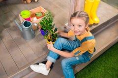 Förtjusande liten flickasammanträde på farstubron och odla den gröna växten i kruka Royaltyfri Foto