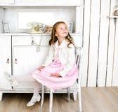Förtjusande liten flickasammanträde på stol Arkivbilder