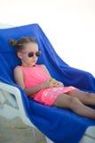 Förtjusande liten flickasammanträde på stol på tropiskt Royaltyfri Fotografi