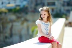 Förtjusande liten flickasammanträde på trappa arkivfoto