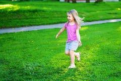 Förtjusande liten flickaspring på ängen Fotografering för Bildbyråer