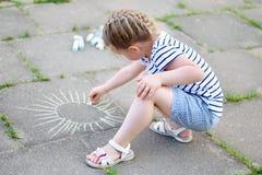 Förtjusande liten flickateckning utanför med krita Royaltyfri Bild