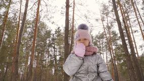 Förtjusande liten flickavåghand till kameran och vinterskogbakgrund arkivfilmer