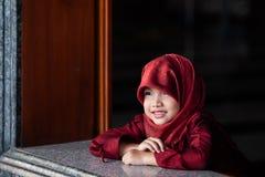 Förtjusande liten muslim flicka i traditionella kläder, röd hijab eller niqab och röd abaya som ut ler och håller ögonen på fönst royaltyfria foton
