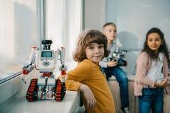 förtjusande liten skolpojke med den diy roboten på stammen arkivbilder