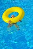 Förtjusande litet barn som kopplar av i simbassäng Arkivbild