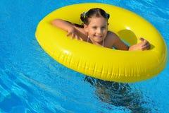 Förtjusande litet barn som kopplar av i simbassäng Arkivfoton