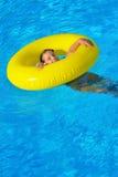 Förtjusande litet barn som kopplar av i simbassäng Royaltyfri Foto