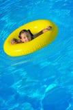 Förtjusande litet barn som kopplar av i simbassäng Royaltyfria Bilder