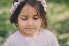 Förtjusande litet barnbarnflicka i ljus - blå elegant dräkt som går och spelar i blommande vårträdgård Royaltyfri Foto