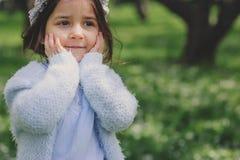 Förtjusande litet barnbarnflicka i ljus - blå elegant dräkt som går och spelar i blommande vårträdgård Royaltyfria Bilder