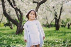 Förtjusande litet barnbarnflicka i ljus - blå elegant dräkt som går och spelar i blommande vårträdgård Arkivfoto