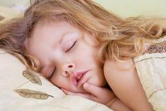Förtjusande litet barnflicka i säng Arkivbild