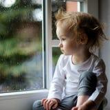 Förtjusande litet barnflicka som ändå ser fönstret Arkivbild
