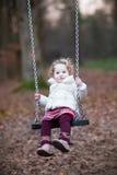 Förtjusande litet barnflicka som har gyckel på en gunga Royaltyfria Bilder