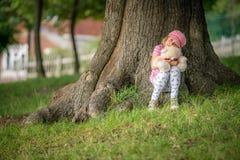 Förtjusande litet barnflicka som kramar hennes favorit- nallebjörn arkivbilder