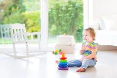 Förtjusande litet barnflicka som spelar i härligt vitt rum arkivbild