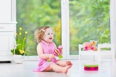 Förtjusande litet barnflicka som spelar maracas i vitt rum Arkivfoton
