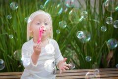 Förtjusande litet barnflickasammanträde på bänken som har gyckel som blåser bubblor Arkivbilder