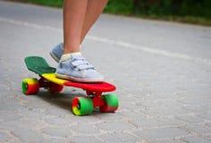Förtjusande litet barnpojke som har gyckel med den färgrika skateboarden utomhus i parkera Fotografering för Bildbyråer