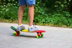 Förtjusande litet barnpojke som har gyckel med den färgrika skateboarden utomhus i parkera Arkivfoton