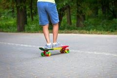 Förtjusande litet barnpojke som har gyckel med den färgrika skateboarden utomhus i parkera Arkivbilder