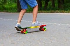 Förtjusande litet barnpojke som har gyckel med den färgrika skateboarden utomhus i parkera Royaltyfria Foton