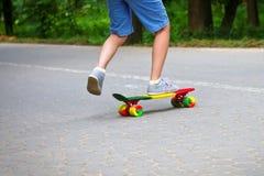 Förtjusande litet barnpojke som har gyckel med den färgrika skateboarden utomhus i parkera Arkivbild