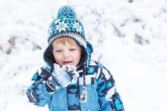 Förtjusande litet barnpojke som har gyckel med snow på vinterdag Arkivfoto
