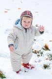 Förtjusande litet barnpojke som har gyckel med snow på vinterdag Arkivbild