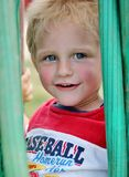 Förtjusande litet barnpojke som kikar till och med vattenhosna Royaltyfri Bild