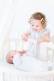 Förtjusande lockig litet barnflicka som talar till den nyfödda brodern arkivfoton