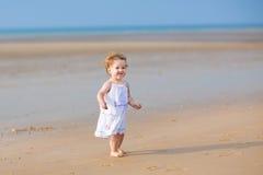 Förtjusande lockigt behandla som ett barn flickan som går på stranden Arkivfoto