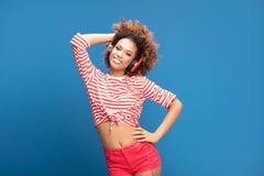Förtjusande lycklig afro flicka med rött skratta för hörlurar arkivfoton