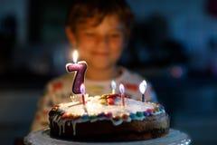 Förtjusande lycklig blond pojke för liten unge som firar hans födelsedag 7 arkivbild