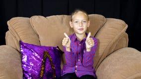 Förtjusande lycklig flicka som talar, visar tummar upp och gör en gest bye-bye lager videofilmer