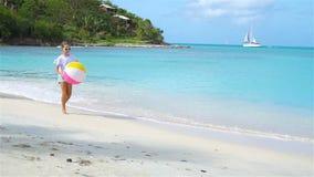Förtjusande lycklig liten flicka på den vita stranden på solnedgången arkivfilmer