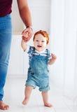 Förtjusande lycklig litet barnpojke som går med hjälpen av fadern Arkivbilder