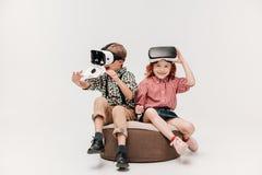 förtjusande lyckliga ungar som använder virtuell verklighethörlurar med mikrofon royaltyfria foton
