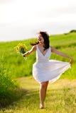 Förtjusande lyckligt sommarkvinnaöverhopp royaltyfri foto