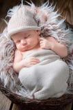 Förtjusande nyfött behandla som ett barn att sova på filten Arkivfoto