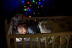 Förtjusande nyfött behandla som ett barn pojken som sover i lathund på natten royaltyfri fotografi
