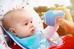 Förtjusande nyfiket behandla som ett barn drinkvatten från flaskan Arkivfoto