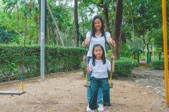 Förtjusande och feriebegrepp: Kvinna- och barnkänsla som är rolig, och lycka på en gunga på lekplatsen arkivfoto