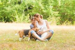Förtjusande pardotter och mamma som sitter på ett gräs med deras husdjur royaltyfria bilder