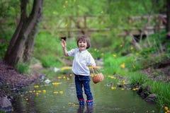 Förtjusande pojke med den lilla korgen som är full av blommor på lite pon Arkivbild
