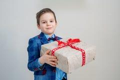 Förtjusande pojke med en gåvaask på en ljus bakgrund arkivfoton