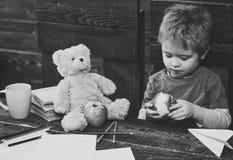 Förtjusande pojke som äter det läckra äpplet Unge som delar mellanmålet med den favorit- leksaken Elev som spelar under avbrott royaltyfri foto